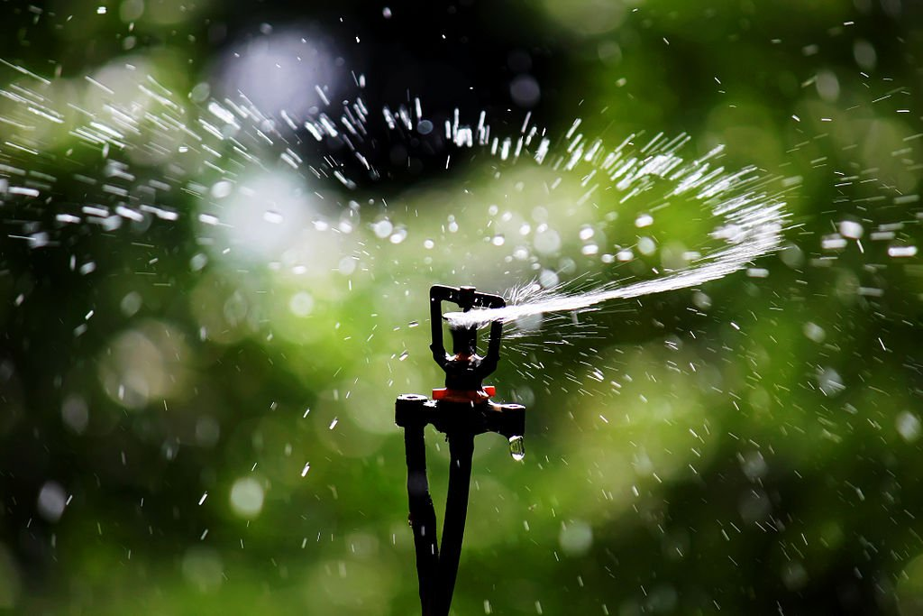 Sprinkler head waters grass in fall